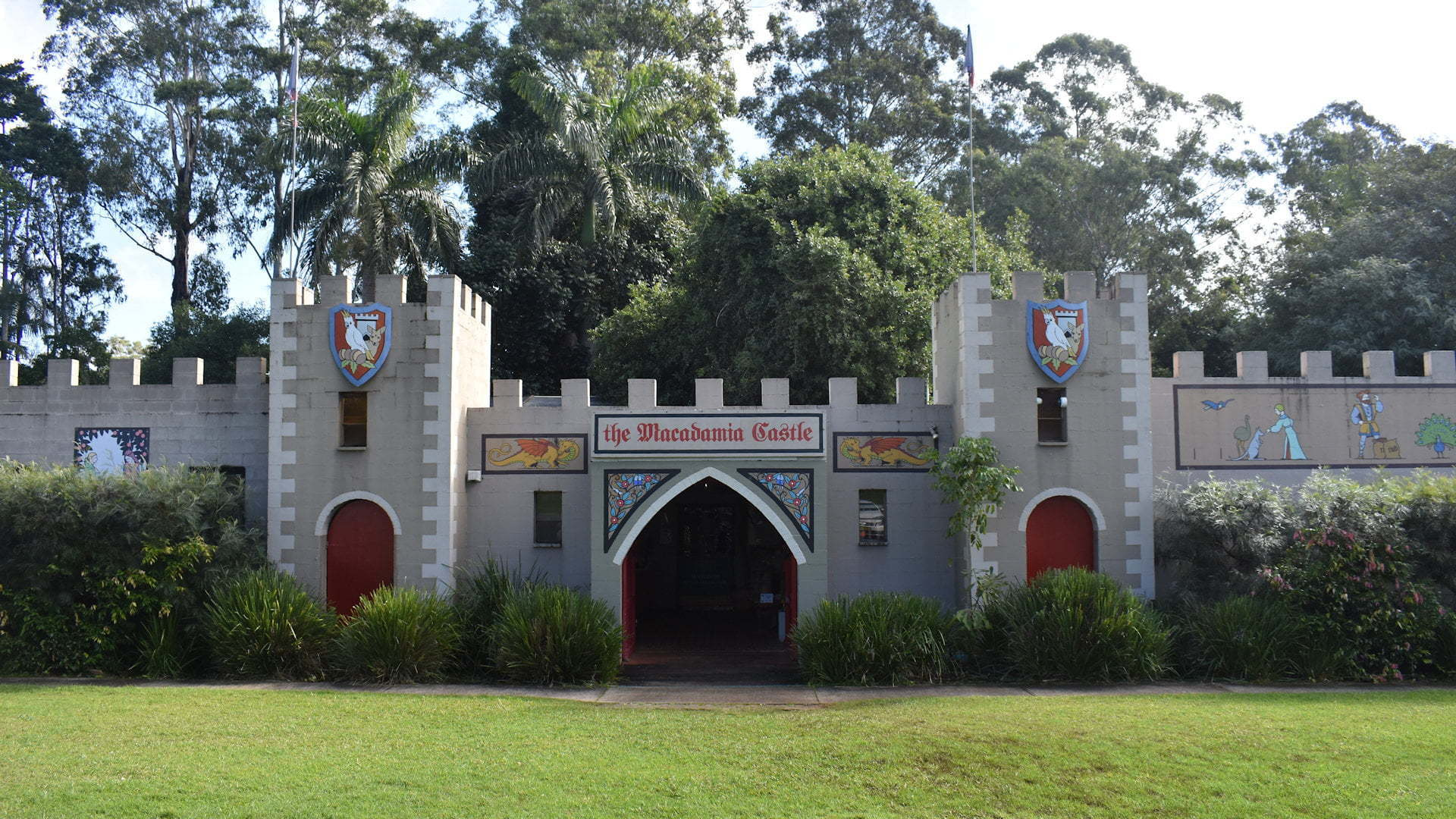 Castle shaped building with entrance in the centre, tower columns either side and walls continuing left and right, taken at the Macadamia Castle north of Ballina