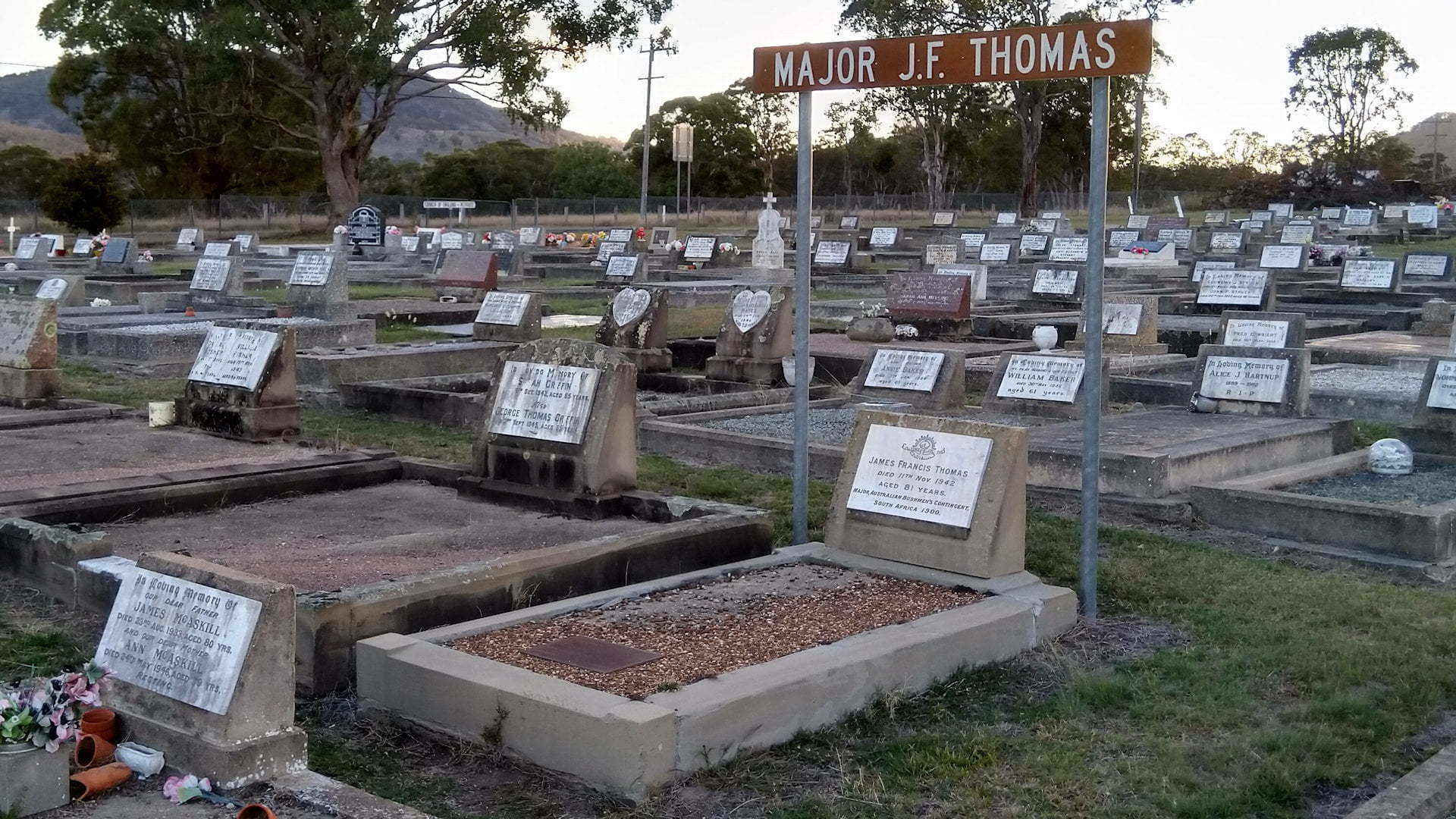Grave in a cemetery with a brown sign above it, Major J.F. Thomas, taken at Tenterfield cemetery