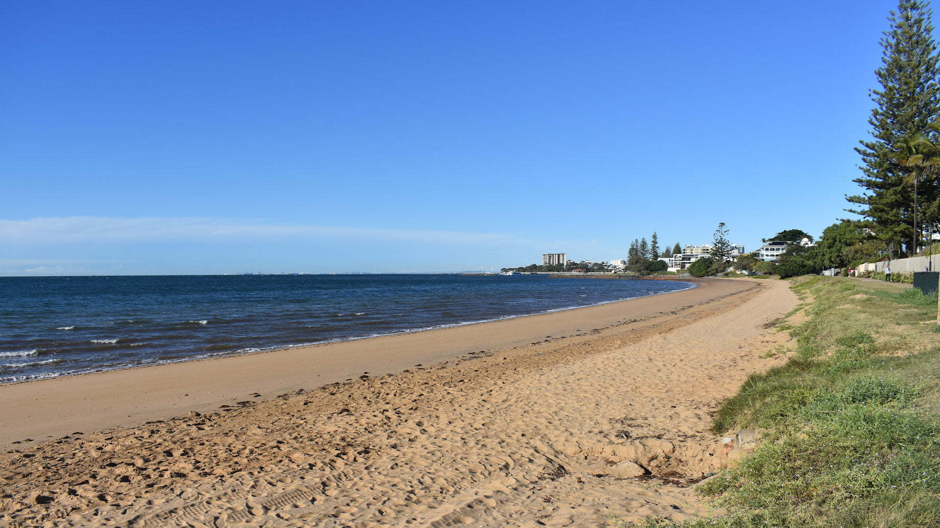Looking along a beach with the water on the left and grass above the sand on the right, taken at Queens Beach on the Redcliffe Peninsula