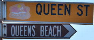 Brown sign for Queens Beach, yellow sign for Queens St