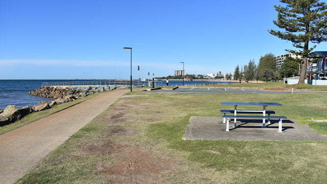 Grass area with a picnic table and pathway running along the side next to water, taken at Queens Beach South on the Redcliffe Peninsula