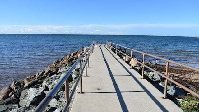 Rock wall jetty extending out to the water with a concrete pathway and metal railings, located at Queens Beach South on the Redcliffe Peninsula