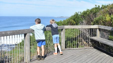 Two boys looking from a viewing platform out to the ocean, taken at Iluka Bluff Lookout