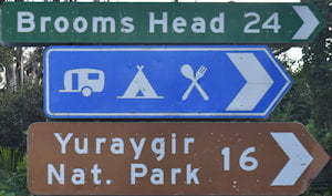 Brown sign for Yuraygir Nat. Park, 16km, green sign for Brooms Head, 24km, blue sign with symbols for caravan, tent, food