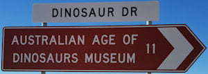 Brown sign for Australian Age Of Dinosaurs Museum, 11km, white sign for Dinosaur Dr