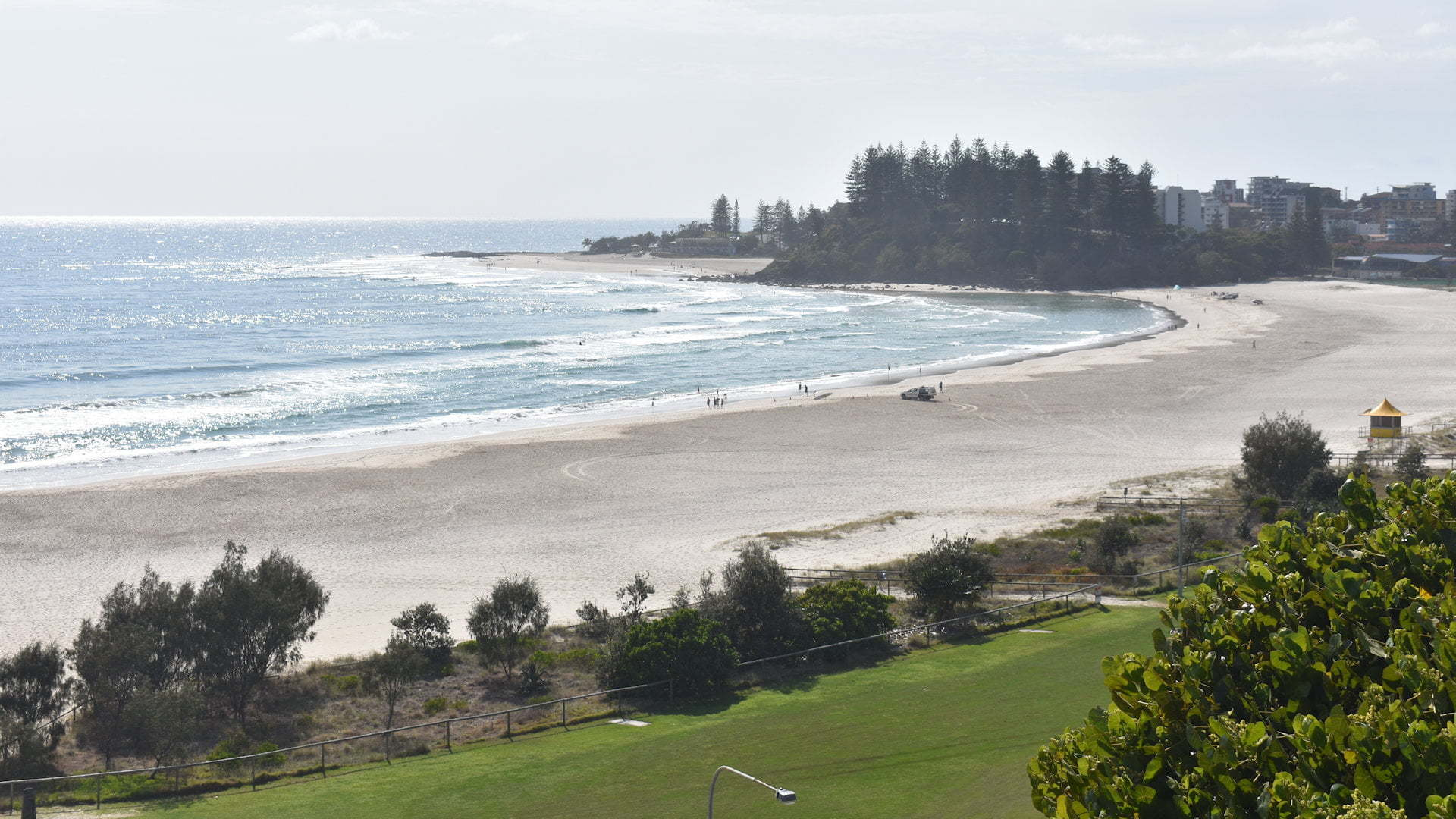 View of Coolangatta Beach showing green grass parkland before the wide sandy beach and the headlands at the other end of the beach