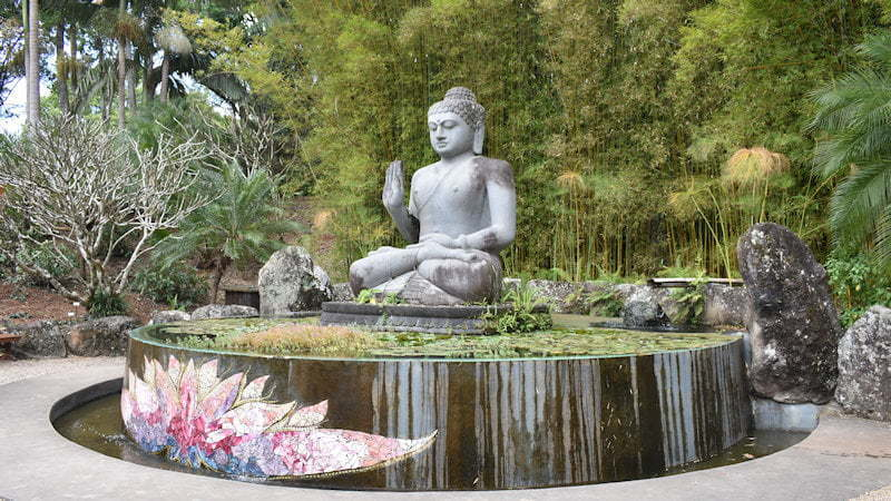 Buddha statue on a pond in the Shambahla Gardens at the Crystal Castle