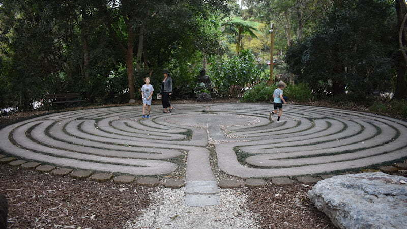 Two boys and a woman walking on the Labyrinth at the Crystal Castle