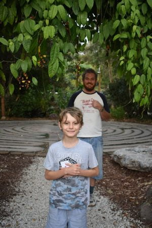 A man and a boy smiling, standing at the entrance of a Labyrinth, at the Crystal Castle