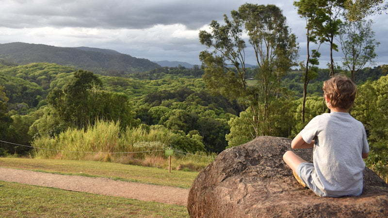 Boy sitting on a rock boulder meditating looking towards rolling hills in the background, taken at the Crystal Castle