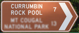 Brown sign for Currumbin Rock Pool, 7km