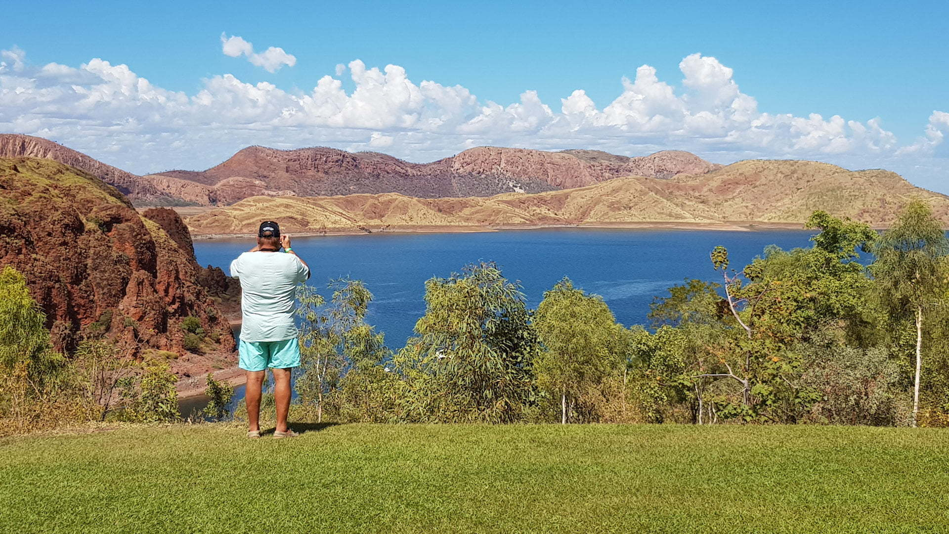 View over Lake Argyle in Western Australia, blue water from the Lake contrasts with the green grass and red rocks