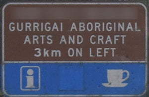 Brown sign for Gurrigai Aboriginal Arts and Craft, 3km on left, blue sign with symbols for information and coffee