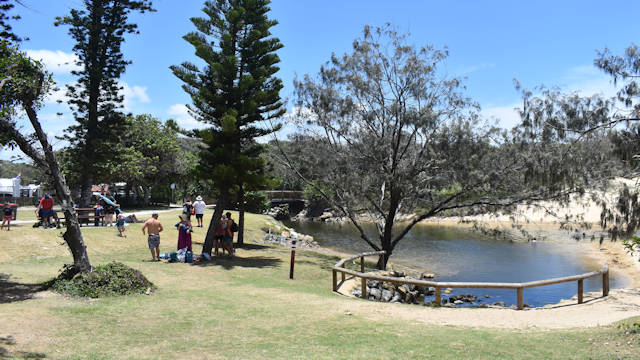 Open grass area, water lagoon to the back, blue skies