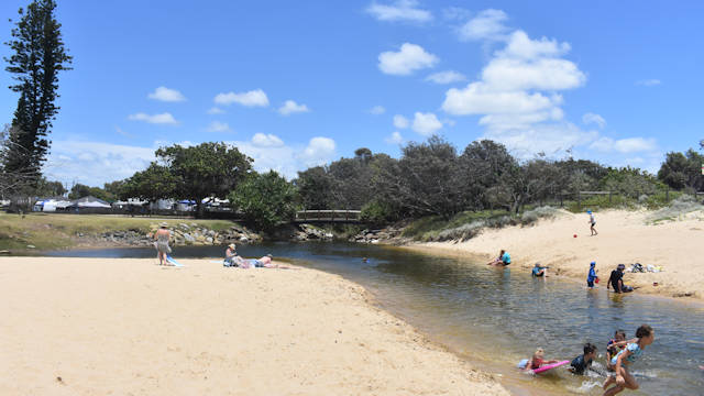 Lagoon and runout channel through sandy beach, looking towards the land, people in the water, blue skies