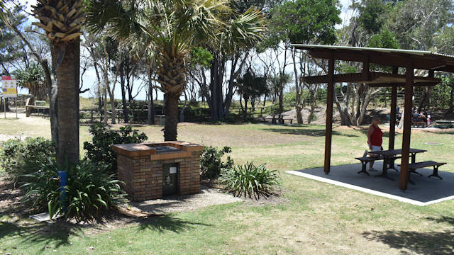 Grass area, free BBQ on the left and a sheltered picnic table to the right