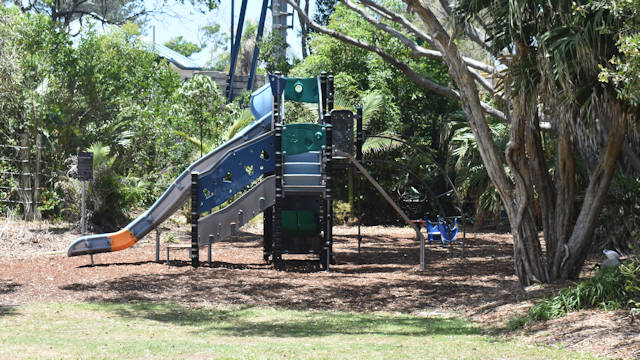 Outdoor playground equipment in a park, shaded by trees