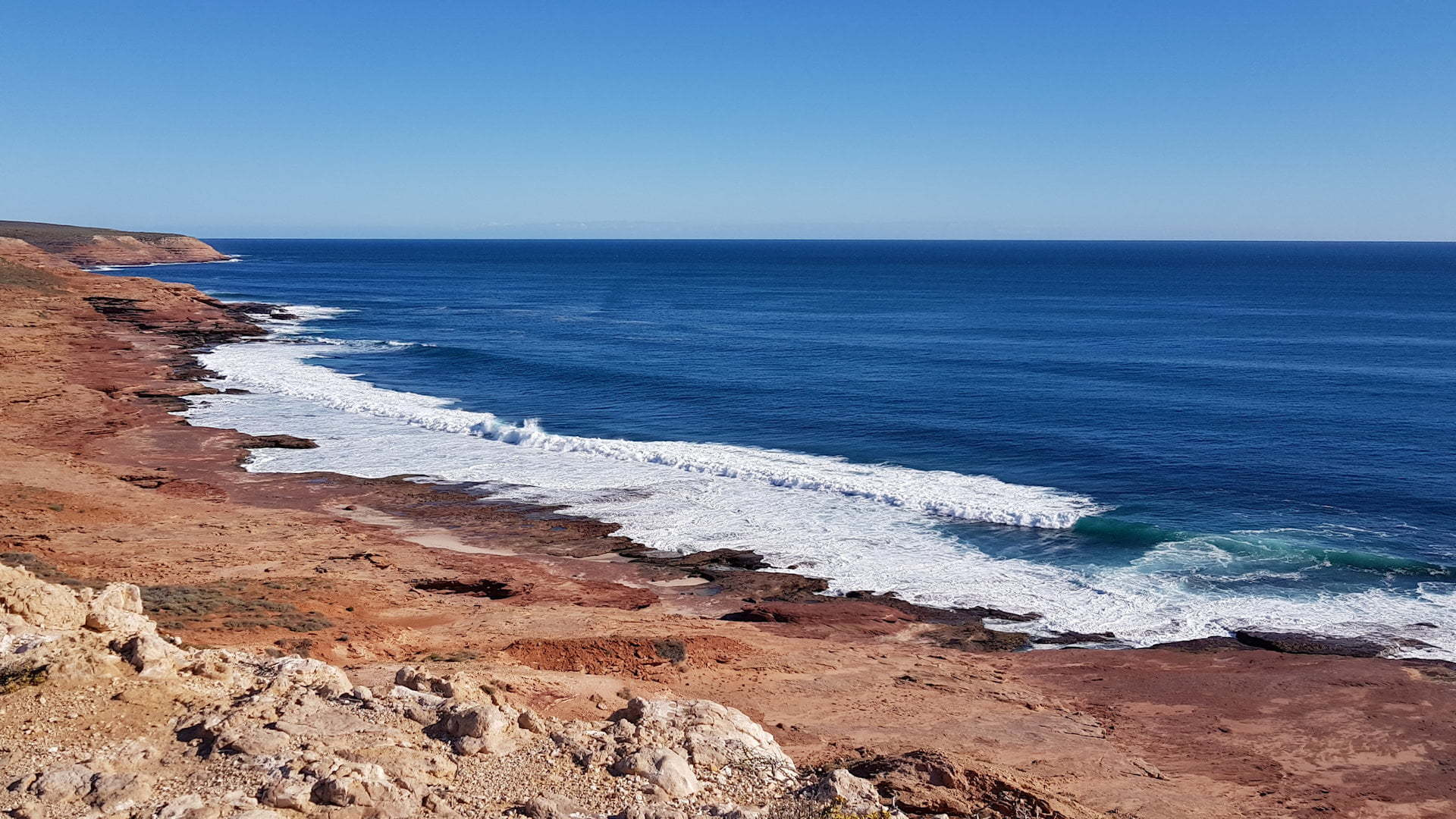 Red cliff coastline with blue ocean and blue sky, taken at Red Bluff in Kalbarri National Park