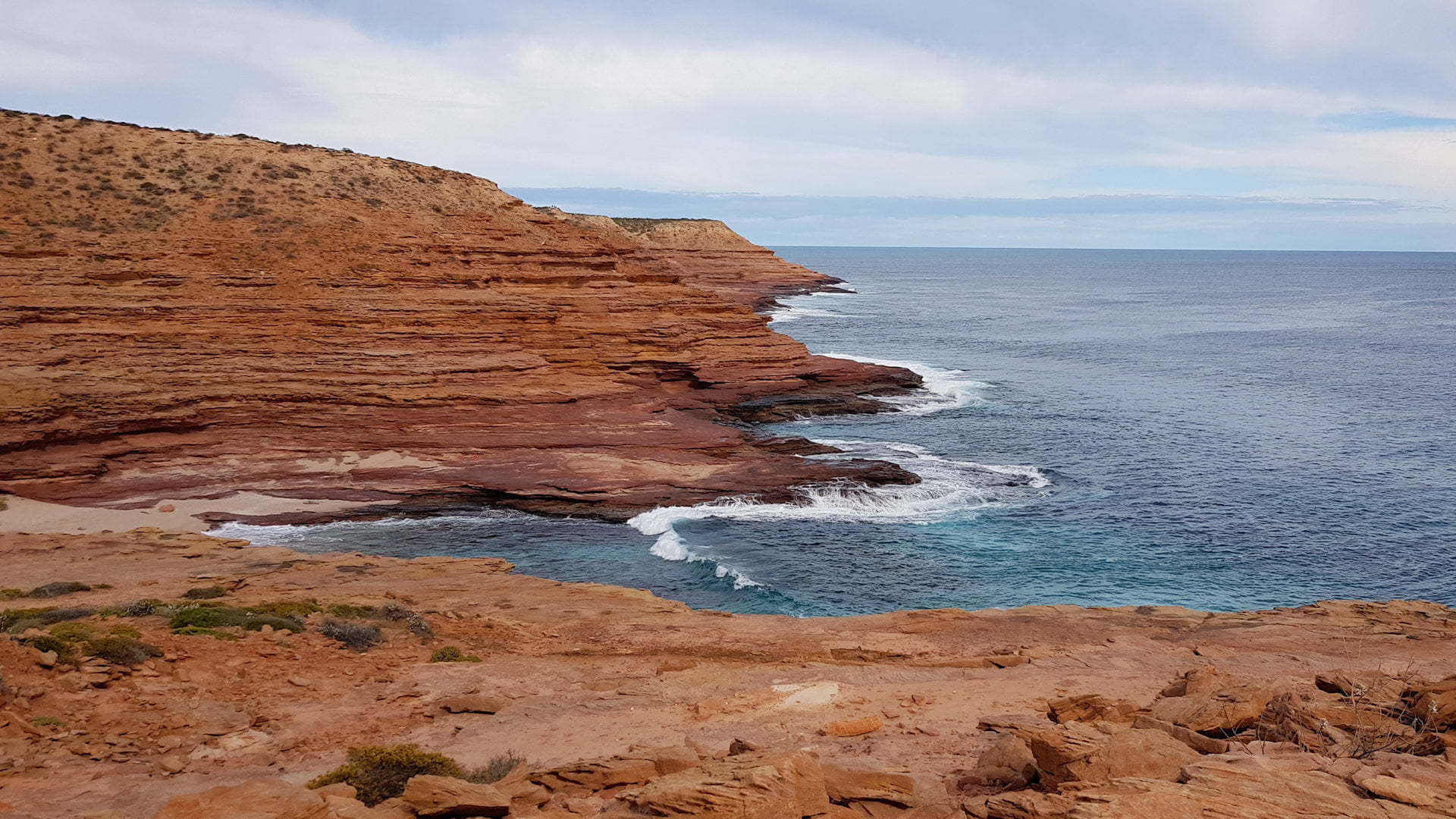 Red sandstone coastline with gorge into the ocean, taken at Pot Alley in Kalbarri National Park in Western Australia