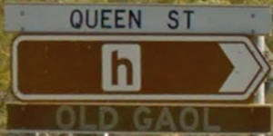 Brown sign for Old Gaol, white sign for Queen St