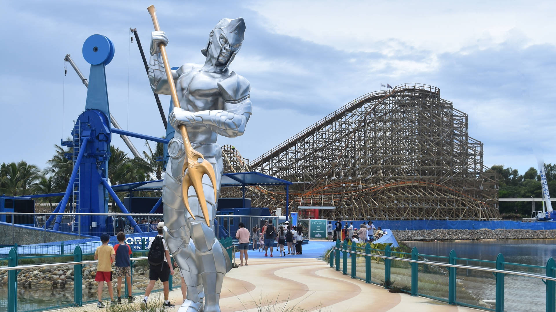 Trident holding silver figure, wooden roller coaster in the background on the right, amusement park ride in the background on the left