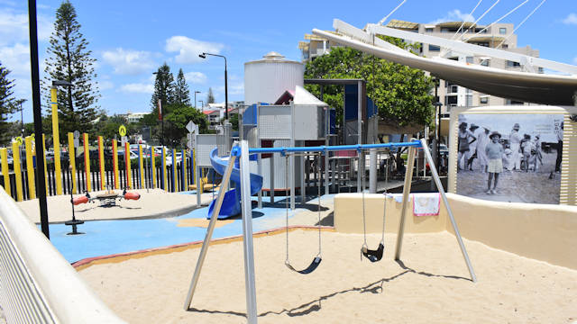 Playground area with swings in the foreground, sea-saw in the background, sandy ground for most of it, climbing structure with a small spiral slippery dip, water tank with an old enlarged photo displayed on the side of it