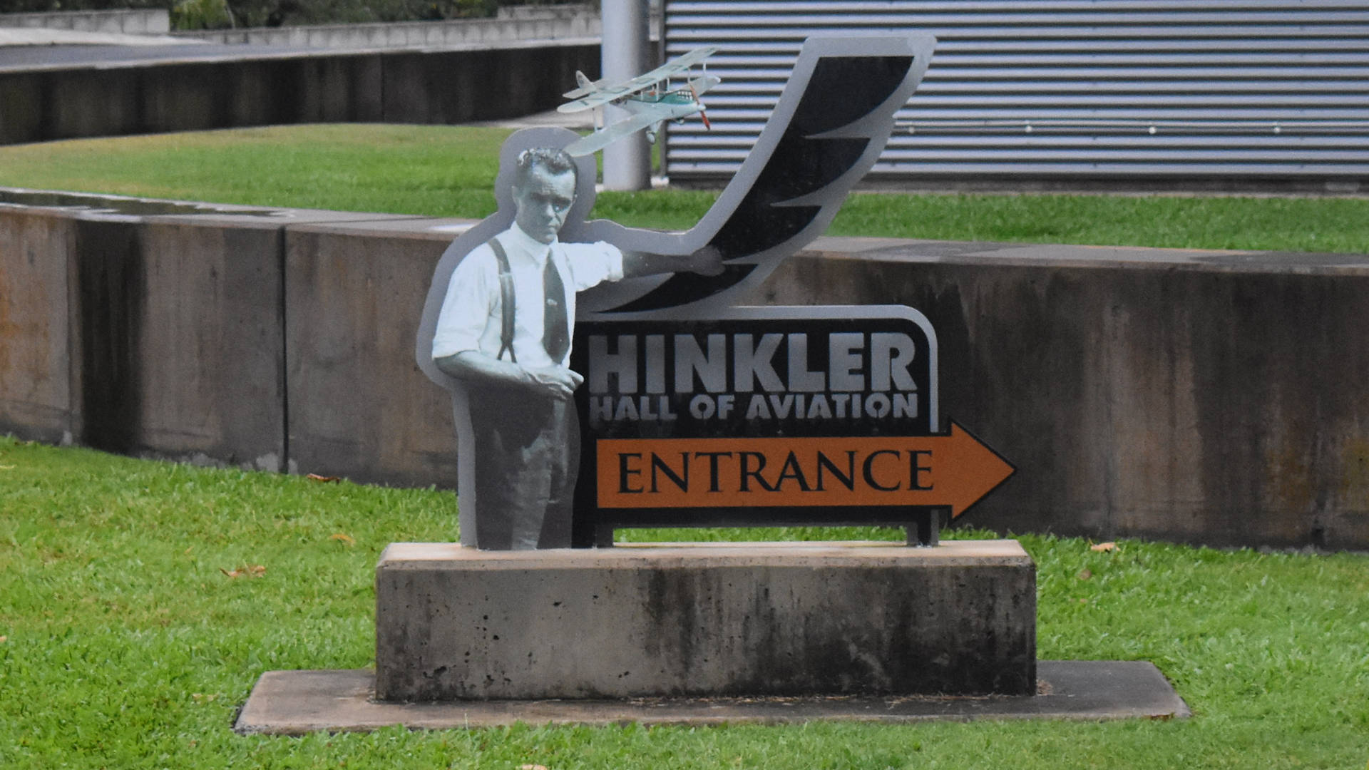Signage for the entrance to Hinkler Hall of Aviation, with an image of Hinkler and his first aircraft