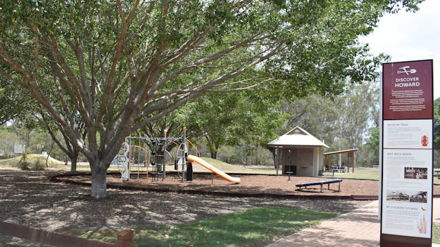 Playground next to a large tree, with an information sign next to a path leading to the playground