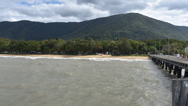 Looking back to a beach from the end of a jetty, mountains in the background, taken from Palm Cove Jetty north of Cairns