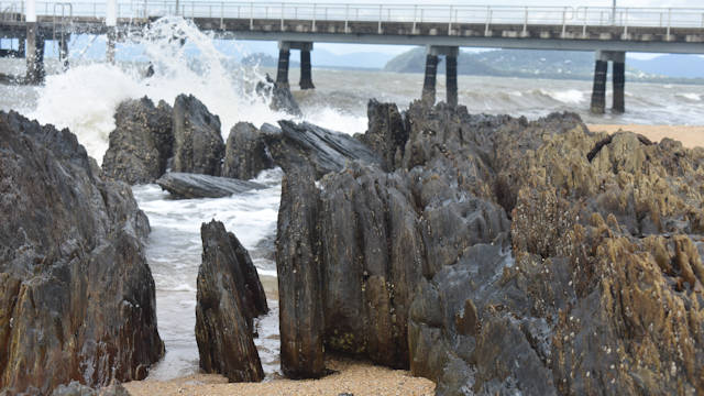 Vertical rocks worn by the ocean, splashing wave over a rock at the back, Palm Cove Jetty in the background