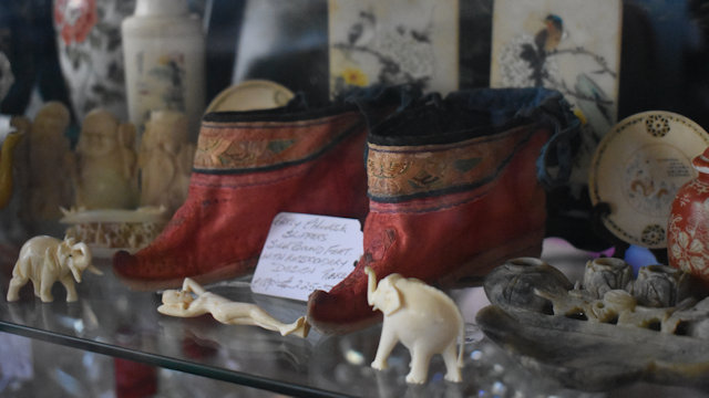 Antique collectibles in a cabinet, Chinese slippers, ivory carvings