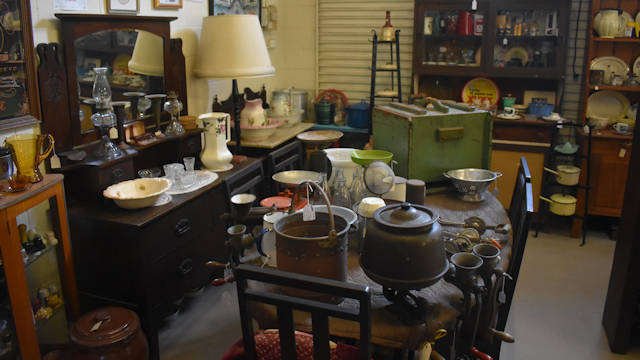 Antique collection with glassware, meat grinders, butter churn, and crockery, sitting on vintage furniture